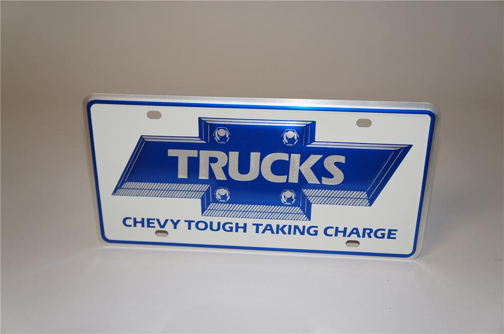 "N.O.S. 1970s-80s Chevy Trucks ""Chevy Tough Taking Charge"" single-sided metal showroom license plate shaped sign. - Front 3/4 - 154427"