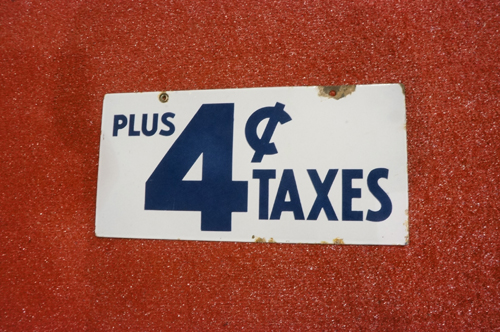 "Addendum Item - 1940's ""Plus 4 Cents Taxes"" double-sided porcelain service station sign. - Front 3/4 - 166642"