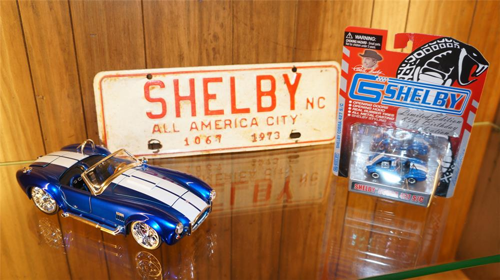 Lot of three Shelby items including two Shelby Cobra die-cast cars and a 1973 Shelby North Carolina sign. - Front 3/4 - 178980