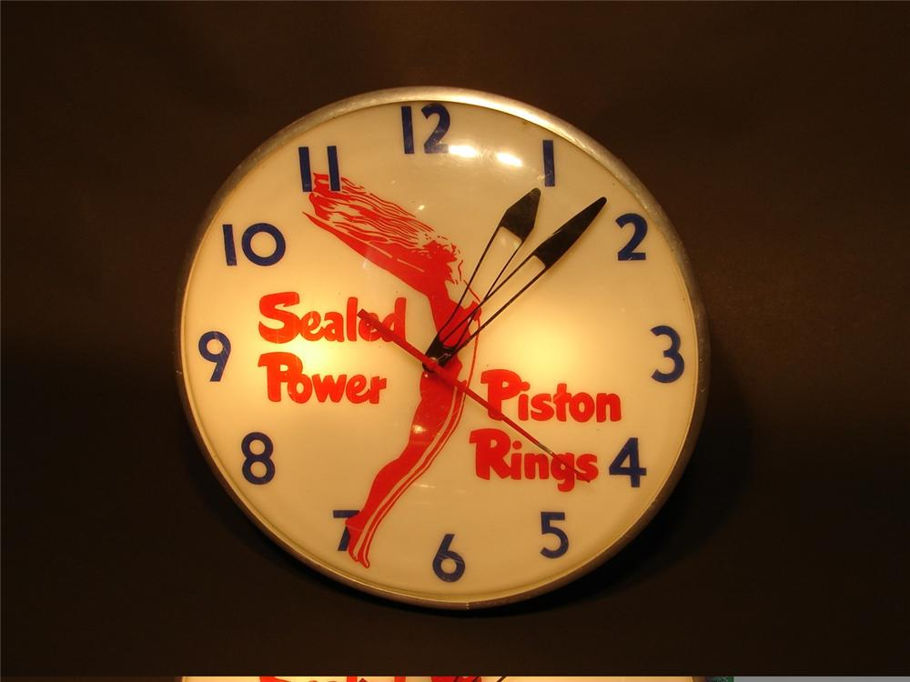 Distinctive 1950s Sealed Power Piston Rings light-up station clock with art deco maiden logo. - Front 3/4 - 45962