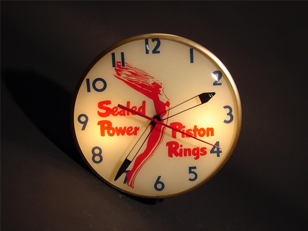 Stunning 1950s Sealed Power Piston Rings light-up station clock with art deco inspired graphics. - Front 3/4 - 50575