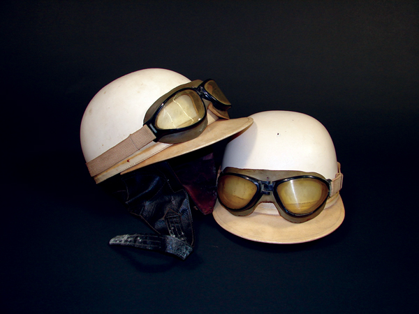 Neat Pair of 1950s grand prix race helmets with goggles attached. - Front 3/4 - 72132